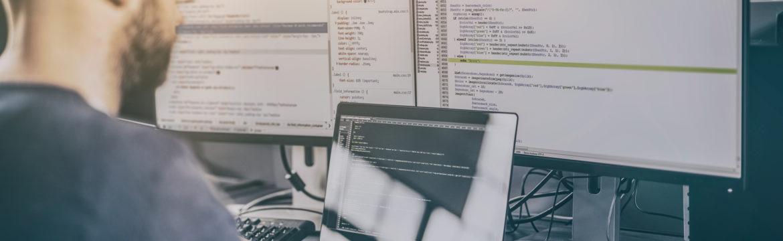 man sitting at desk writing programming code